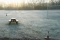 Bench and bollards on empty soccer field at sunset