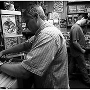 Tony Miles, left, a customer of sixteen years, looks through comic books as David Tilley walks by shortly before closing at Nostalgia Newsstand.