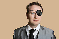 Close-up of a young businessman with eye patch looking away over colored background
