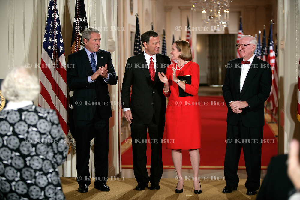 President Bush looks on as John Roberts is sworn in as the 17th Chief Justice of the US Supreme Court by Associate Justice John Paul Stevens Thursday, September 29, 2005, in the East Room of the White House.  Also attending is Roberts's wife, Jane Sullivan Roberts...Photo by Khue Bui
