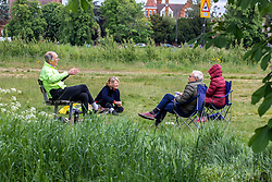 © Licensed to London News Pictures. 13/05/2020. London, UK. Members of the public with camp chairs and tea mugs social distancing while out on Wimbledon Common as the Government relaxes the law on lockdown today to let people spend more time outside to enjoy the fresh air, picnics, sunbathing and meet other people while following social distancing guidelines. Photo credit: Alex Lentati/LNP