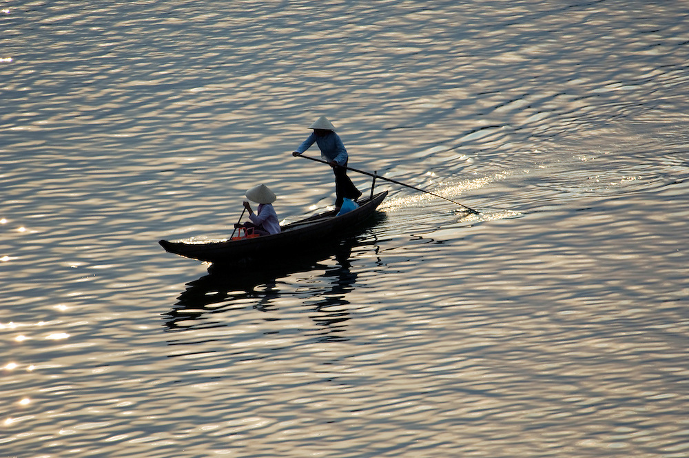 Vietnam: A boat taxi is rowed by a woman to ferry her passenger across the Perfume River, Hue.