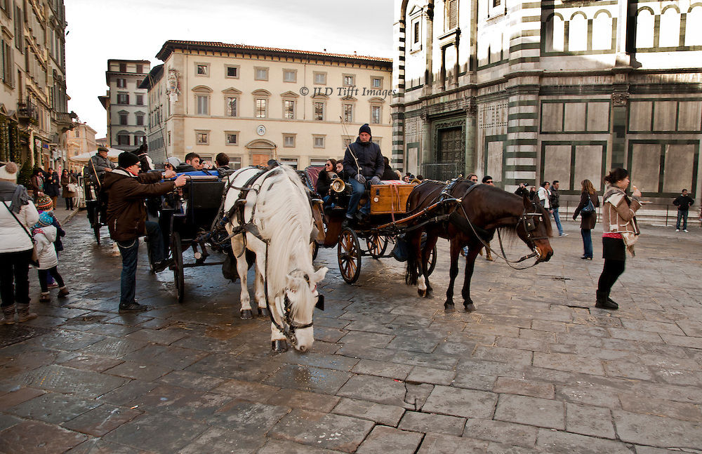 The Baptistry is also Romanesque, built in the 11th and 12th centuries.  Horse drawn carriages wait for passengers in the Piazza del Duomo, north side of the Baptistry,  Three carriages with horses and drivers have taken on passengers and are about to leave.  A few pedestrians are scattered about.