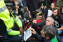 London, UK. 16 October, 2019. A Metropolitan Police officers prepare to arrest Jonathan Bartley (c), co-leader of the Green Party, Guardian journalist George Monbiot (r) and a group of climate activists from Extinction Rebellion using Section 14 of the Public Order Act 1986 after they sat in the road in Whitehall following a People's Assembly in Trafalgar Square as part of a protest against the use by the Metropolitan Police of Section 14 so as to prohibit entirely Extinction Rebellion Autumn Uprising protests throughout the capital.