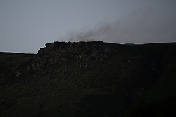 "© Licensed to London News Pictures . 28/06/2018 . Saddleworth , UK . Fire is seen burning above a rocky peak , known locally as "" Indian's Head "" . The army are being called in to support fire-fighters , who continue to work to contain large wildfires spreading across Saddleworth Moor and affecting people across Manchester and surrounding towns . Very high temperatures , winds and dry peat are hampering efforts to contain the fire , described as "" unprecedented "" by police and reported to be the largest in living memory . Photo credit: Joel Goodman/LNP"