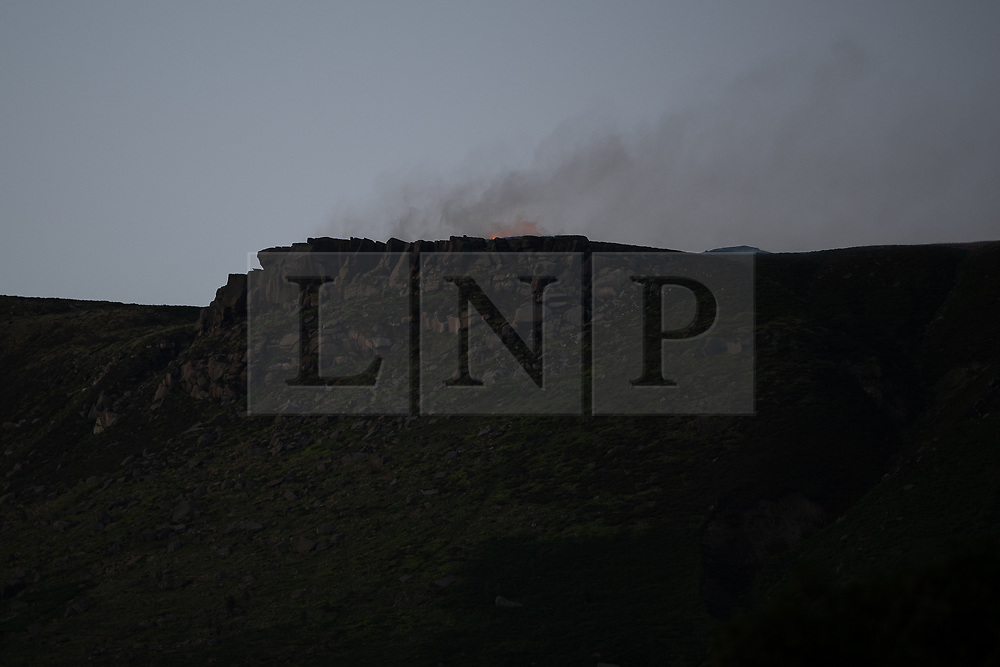 """© Licensed to London News Pictures . 28/06/2018 . Saddleworth , UK . Fire is seen burning above a rocky peak , known locally as """" Indian's Head """" . The army are being called in to support fire-fighters , who continue to work to contain large wildfires spreading across Saddleworth Moor and affecting people across Manchester and surrounding towns . Very high temperatures , winds and dry peat are hampering efforts to contain the fire , described as """" unprecedented """" by police and reported to be the largest in living memory . Photo credit: Joel Goodman/LNP"""