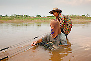 "07 APRIL 2010 - NAKHON PHANOM, THAILAND:  A couple nets fish in a channel in the Mekong River. They said they used to have use a boat for this but now the river is so low they do it on foot. He said he doesn't know why the river is so low, that some people say it's global warming. ""But I don't know what that is. I think it's when the factories send too much smoke into the air, but I don't understand it."" He went onto to say that they catch much fewer fish now than they did in the past. Normally the river flows completely through the river bed but it's currently running through a channel in the bottom of the river bed. According to people who live here, the river is at its lowest point in nearly 50 years. Many of the people who live along the river farm and fish. They claim their crops yields are greatly reduced and that many days they return from fishing with empty nets. The river is so shallow now that fisherman who used to go out in boats now work from the banks and sandbars on foot or wade into the river.     PHOTO BY JACK KURTZ"