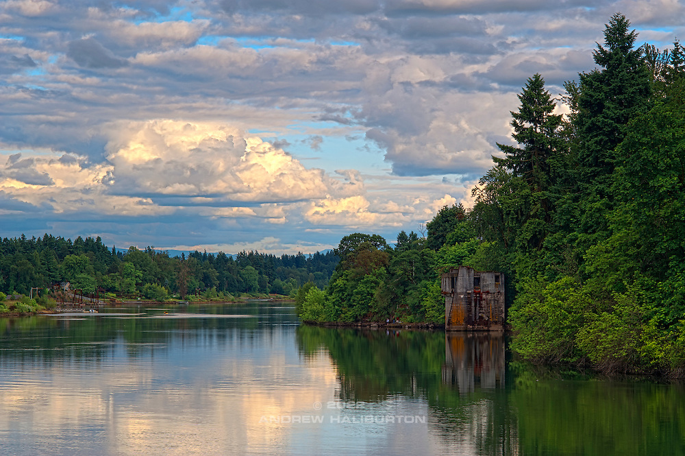 Scenic view of the Willamette River, bank full from spring snowmelt.  Looking south from George Rogers Park in Lake Oswego.  The concrete structure in the river was a log hoist built in 1905 by Crown Willamette Paper Company and operated until the 1920s.  More recently, the private owner abandoned an attempt to improve it as a residence and today it lies abandoned.