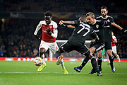 Arsenal's Bukayo Saka (87) goes past Qarabag FK's Wilde-Donald Guerrier (77) during the Europa League group stage match between Arsenal and FK QARABAG at the Emirates Stadium, London, England on 13 December 2018.