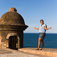 Portrait of woman standing and smiling by turret of San Cristobal Castle, Old San Juan, Puerto Rico.
