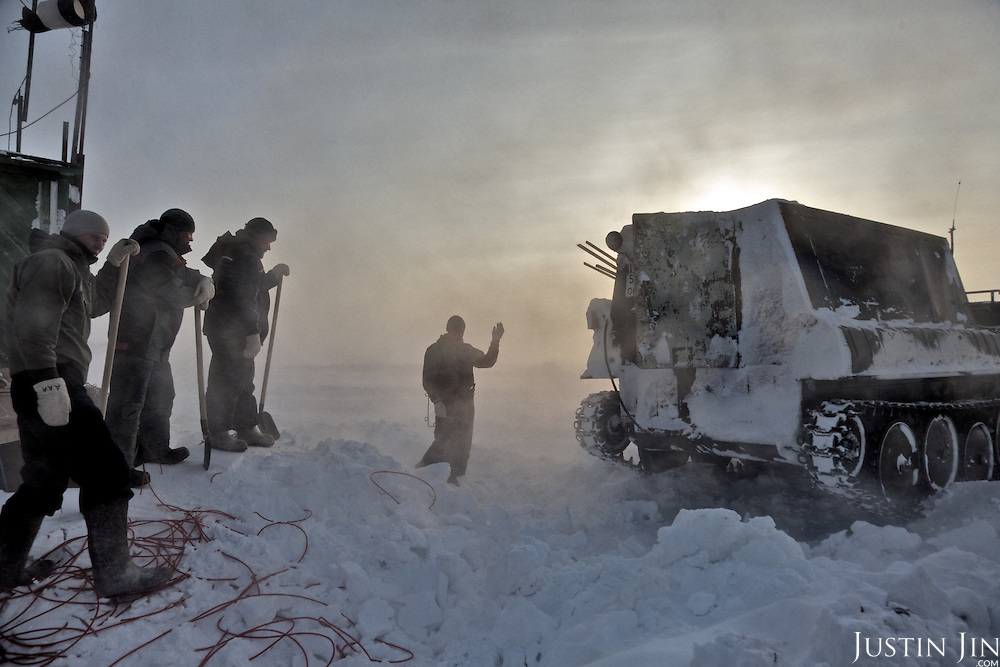 "Workers signal a snow tank to reverse in the colony set up by oil and gas prospecting company ""Siesmorevzedka"" in the Arctic tundra. Typically, they work in the cold, isolated Arctic tundra for the entire winter, returning to civilisation only in spring."