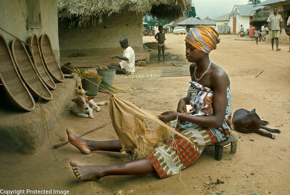 Village life in Africa: West Africa, Liberia, Kpelle tribe: young woman weaving a bag from raphia palm fiber in village.