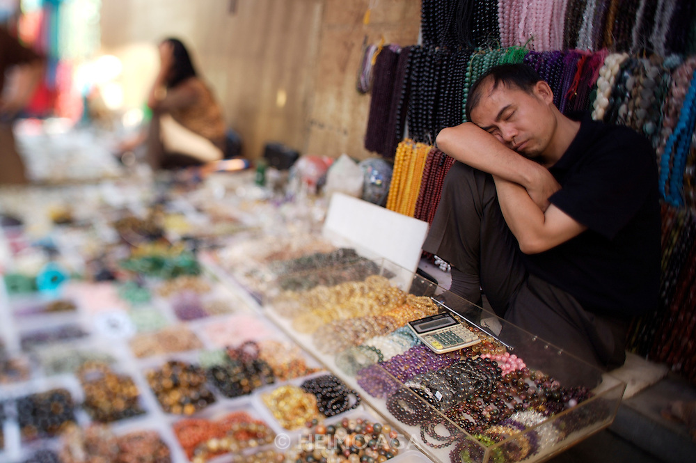 Panjiayuan weekend market. Glas pearl shop owner having a nap..