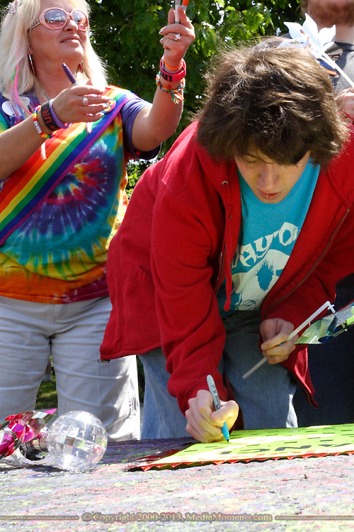 Judy Ward of Kettering hands out markers as Steven Powell of Moraine adds his name to a sign he will carry during the annual Dayton Pride Parade and Festival in downtown Dayton, Saturday, June 2, 2012.