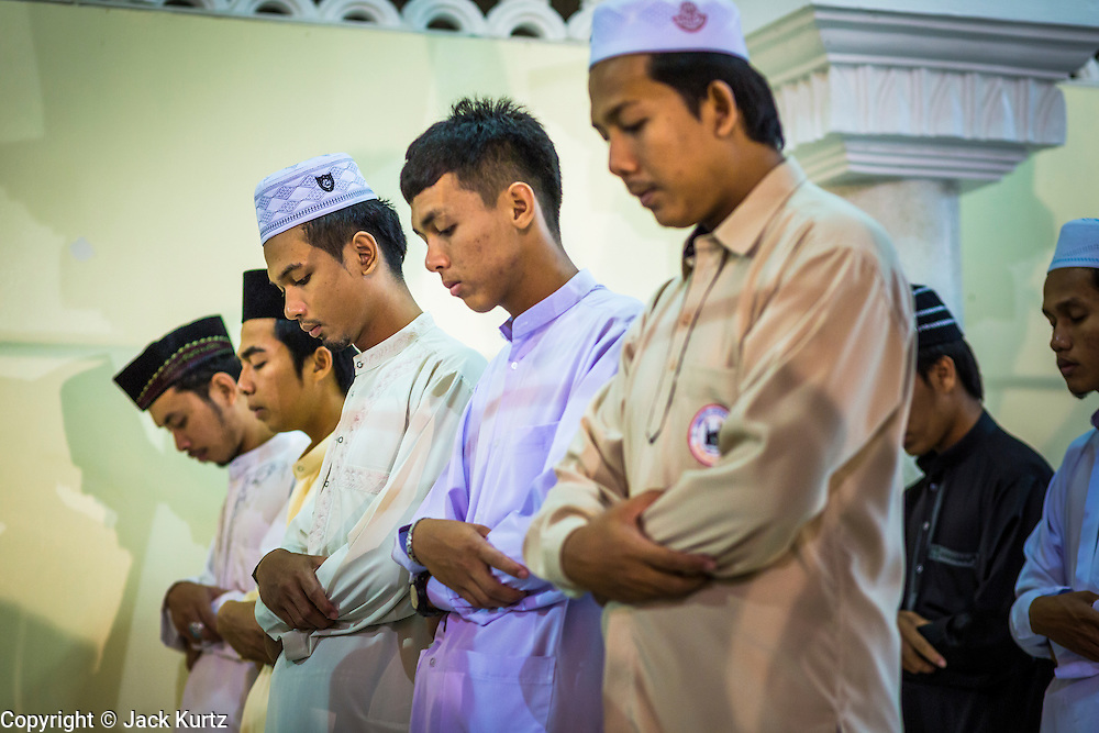 11 JULY 2013 - PATTANI, PATTANI, THAILAND:  Men pray outside of Pattani Central Mosque in Pattani, Thailand, Thursday night for Ramadan services. The mosque is one of the busiest in south Thailand. About 15,000 people attend nightly Ramadan services in the mosque. Ramadan is the ninth month of the Islamic calendar, and the month in which Muslims believe the Quran was revealed. Muslims believe that the Quran was sent down during this month, thus being prepared for gradual revelation by Jibraeel (Gabriel) to the Prophet Muhammad. The month is spent by Muslims fasting during the daylight hours from dawn to sunset. Fasting during the month of Ramadan is one of the Five Pillars of Islam.     PHOTO BY JACK KURTZ