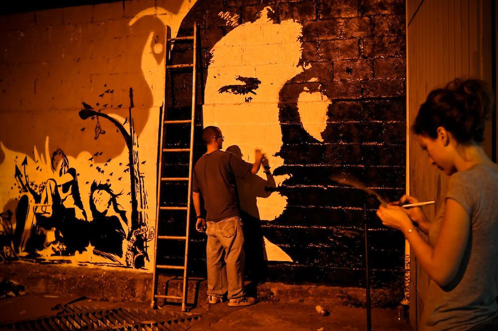 """(Left) Urban artist """"ERGO"""" works on a stencil in Caracas, Venezuela."""