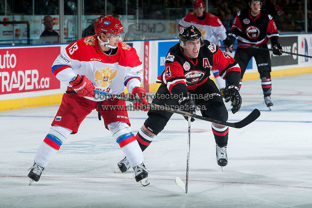KELOWNA, CANADA - NOVEMBER 9: Kirill Pilipenko #13 of Team Russia skates with the puck with Haydn Fleury #4 of Team WHL in pursuit on November 9, 2015 during game 1 of the Canada Russia Super Series at Prospera Place in Kelowna, British Columbia, Canada.  (Photo by Marissa Baecker/Western Hockey League)  *** Local Caption *** Kirill Pilipenko; Haydn Fleury;