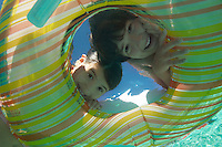 Boy and girl looking through inflatable raft in swimming pool, underwater view