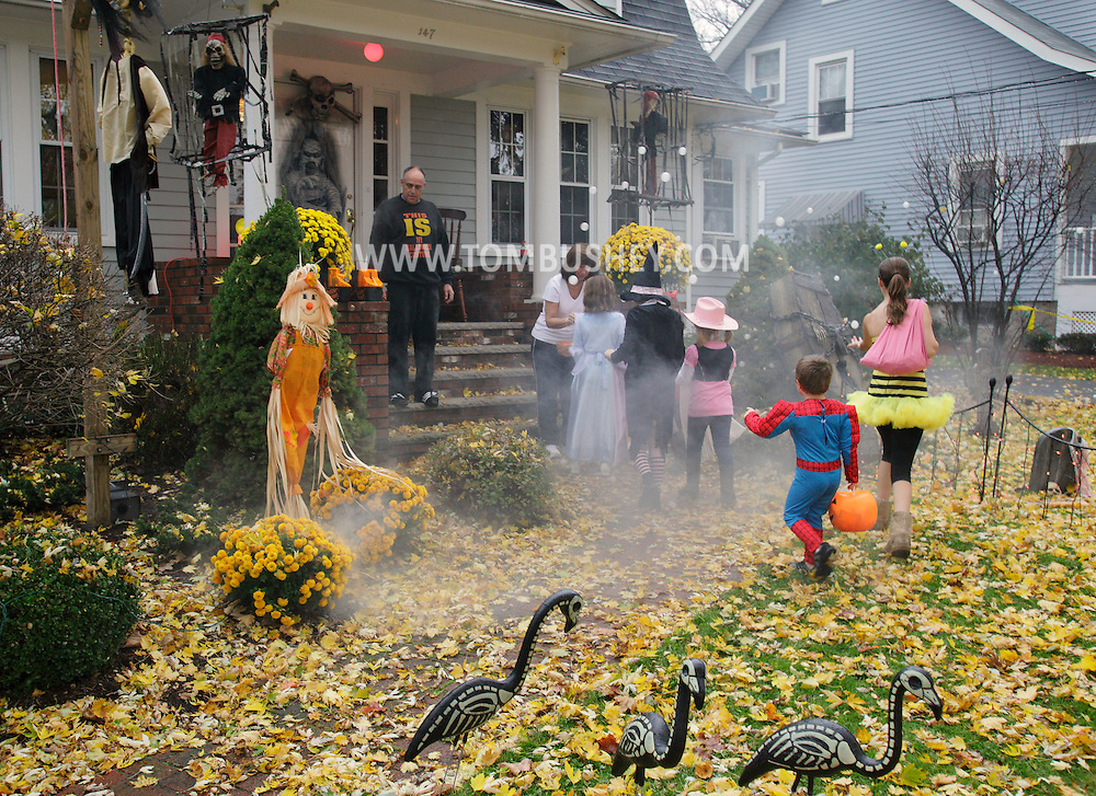 Goshen, NY - Chilldren in costume trick or treat at a house with an elaborate Halloween display in the front yard on Oct. 31, 2009.