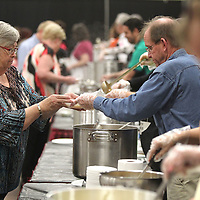 Adam Robison | BUY AT PHOTOS.DJOURNAL.COM<br /> Pat Hamilton, of Nettleton, is handed her bowl of soup by Mike Muphree, who is serving for the Neon Pig, during the Empty Bowls Luncheon Wednesday morning at Building V of the Tupelo Furniture Market.