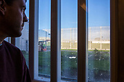 A prisoner looks out of his cell window at the sunshine. HMP/YOI Portland, Dorset. A resettlement prison with a capacity for 530 prisoners. Dorset, United Kingdom.