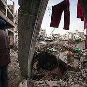 """Shejaya, quartiere a nord della striscia di Gaza. Una delle zone piu colpite dall'attacco israeliano """"Margine protettivo"""". Il quartiere è stato raso al suolo. La popolazione, a distanza di sei mesi dalla fine della guerra, vive tra le macerie della propria casa, al freddo, senza luce, gas e acqua. Nella foto all'esterno di una casa, tra le macerie, panni stesi che denotano come le persone continuino a vivere dentro le case distrutte, arrangiandosi con delle tende per proteggersi dal freddo."""