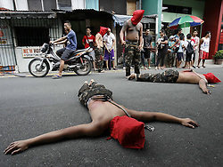61396079<br /> Penitents lie on the ground to pray during a Holy Week ritual to atone for their sins, on a street in Mandaluyong City, the Philippines, Thursday, 17th April 2014. Picture by  imago / i-Images<br /> UK ONLY