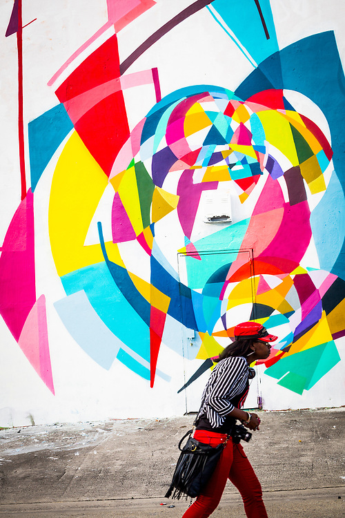 Man strides past mural in Miami's Wynwood arts district