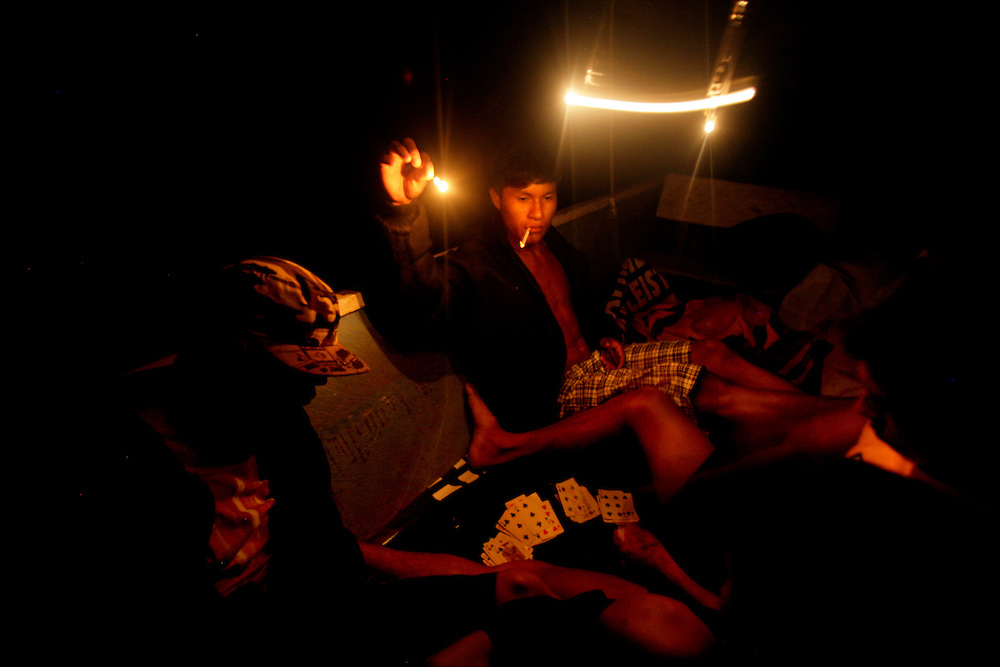 Three Kichwa boys play cards while they fish at night in the Napo River near the community of San Pedro Sumino.   They caught five carachamas (a type of fish) and one pirhana.