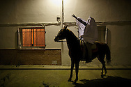 """A horseman cheer during the """"La Encamisa"""" Festival on December 7,  2014 in Torrejoncillo, Extremadura region, Spain. """"La Encamisa"""" is an ancient festival in honor of Immaculate Conception. Hundreds of horsemen wearing a white sheet gather outside the church in the main square. The procession starts when a banner with the image of Immaculate Conception is delivered to the horse rider steward and people cheer and shoot blanks. There are bonfires along the way where people gather to chat, eat traditional sweets and drink local wine. The origin of this tradition is unknown but it is believed the festival comes from a military event in which people from Torrejoncillo were involved. The war in Flanders in 1585, the Battle of Pavia or a legend of the siege suffered by city of Coria. (© Pablo Blazquez)"""