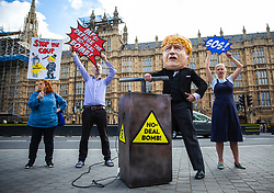 "© Licensed to London News Pictures. 03/09/2019. London, UK. Campaigners from Avaaz hold a photocall outside Parliament with a man dressed as Prime Minister Boris Johnson pushing the plunger on a ""No-Deal Bomb"". MPs return from recess today and may vote on legislation to block a no deal exit from the European Union. Photo credit: Rob Pinney/LNP"