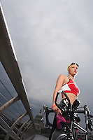 Triathlon athlete holding bike standing on footbridge low angle view Millennium Bridge London England