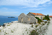 Partially damaged stone and tile building, island of Vrnik, Croatia