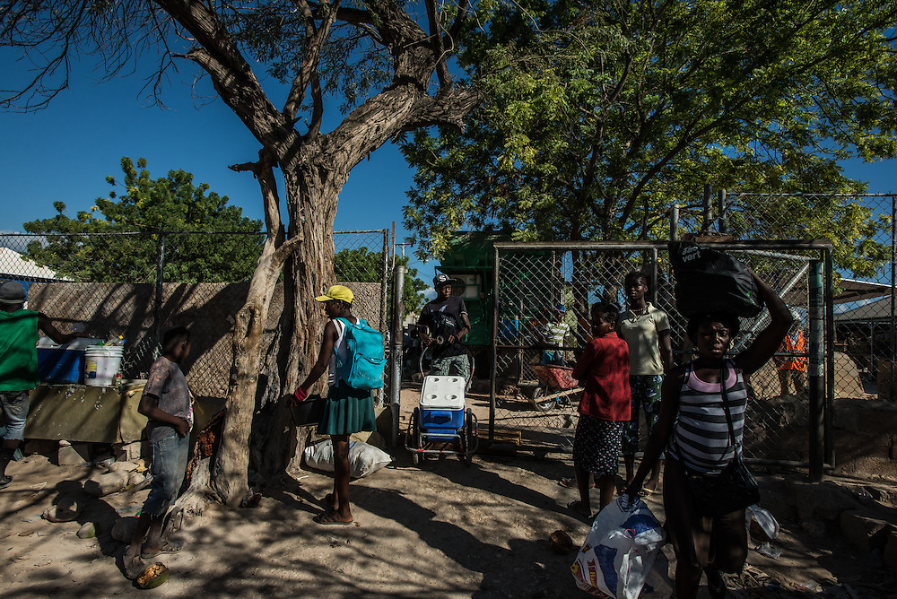 PEDERNALES, DOMINICAN REPUBLIC - NOVEMBER 23, 2015: Vendors pass through the fence that marks the border between Anse-A-Pitre, Haiti and Pedernales, Dominican Republic.  PHOTO: Meridith Kohut for The New York Times