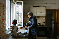 "SUTERA, ITALY - 8 JANUARY 2018: Margareth (30), a Nigerian asylum seeker who arrived in Sutera in 2015, cooks lunch for her children in her apartment, in Sutera, Italy, on January 8th 2018.<br /> <br /> Sutera is an ancient town plastered onto the side of an enormous monolithic rock, topped with a convent, in the middle of the western half of Sicily, about 90 minutes by car south of the Sicilian capital Palermo<br /> Its population fell from 5,000 in 1970 to 1,500 today. In the past 3 years its population has surged  after the local mayor agreed to take in some of the thousands of migrants that have made the dangerous journey from Africa to the Sicily.<br /> <br /> ""Sutera was disappearing,"" says mayor Giuseppe Grizzanti. ""Italians, bound for Germany or England, packed up and left their homes empty. The deaths of inhabitants greatly outnumbered births. Now, thanks to the refugees, we have a chance to revive the city.""<br />  Through an Italian state-funded project called SPRAR (Protection System for Refugees and Asylum Seekers), which in turn is co-funded by the European Union's Fund for the Integration of non-EU Immigrants, Sutera was given financial and resettlement assistance that was co-ordinated by a local non-profit organization called Girasoli (Sunflowers). Girasoli organizes everything from housing and medical care to Italian lessons and psychological counselling for the new settlers.<br /> The school appears to have been the biggest beneficiary of the refugees' arrival, which was kept open thanks to the migrants.<br /> Nunzio Vittarello, the coordinator of the E.U. project working for the NGO ""I Girasoli"" says that there are 50 families in Sutera at the moment."