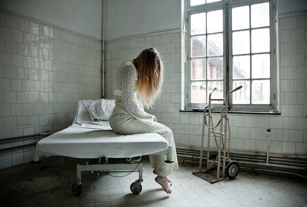 woman sitting on bed in a abandoned mental hospital