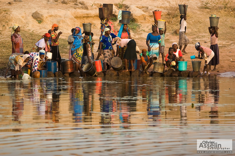 People fill containers with water at the Dikunani dam in Savelugu, northern Ghana, on Friday March 9, 2007. The only of four water sources that has not completely dried out around Savelugu, the pond is used by hundreds of people daily who sometimes walk several kilometers to fetch water. Despite the presence of mesh filters available to people who come get water, cases of guinea worm in the area have gone up sharply in the recent months.