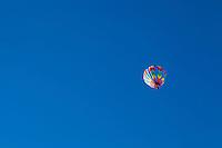A single hot air balloon in a clear blue sky, Albuquerque, New Mexico, USA.  Hot air Balloon Fiesta, October, 2010.