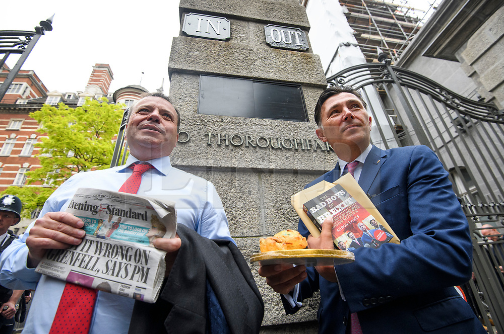 """© Licensed to London News Pictures. 12/06/2018. London, UK. Leave.EU founder ARRON BANKS and Leave.EU campaigner ANDY WIGMORE stand next to """"IN"""" and """"OUT"""" signs as they arrive at Portcullis House in London where they are due to give evidence to a Commons Digital, Culture, Media and Sport Committee about fake news. The pair have been accused of collusion with Russian officials around the time of the Brexit referendum. Photo credit: Ben Cawthra/LNP"""