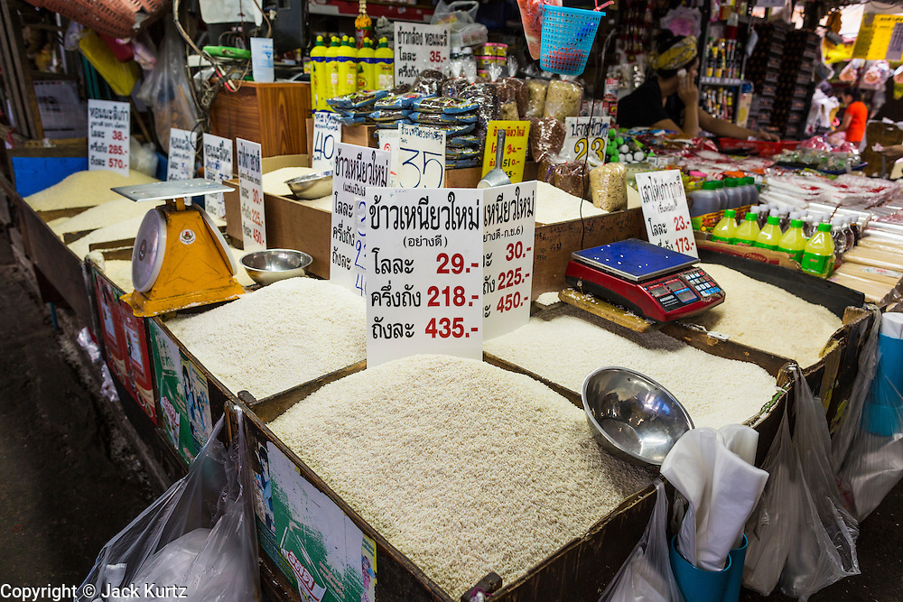 "24 AUGUST 2013 - BANGKOK, THAILAND:     A rice seller sets up his market stall in Khlong Toei Market in Bangkok. Thailand entered a ""technical"" recession this month after the economy shrank by 0.3% in the second quarter of the year. The 0.3% contraction in gross domestic product between April and June followed a previous fall of 1.7% during the first quarter of 2013. The contraction is being blamed on a drop in demand for exports, a drop in domestic demand and a loss of consumer confidence. At the same time, the value of the Thai Baht against the US Dollar has dropped significantly, from a high of about 28Baht to $1 in April to 32THB to 1USD in August.    PHOTO BY JACK KURTZ"