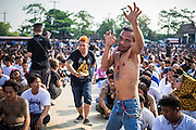 """23 MARCH 2013 - NAKHON CHAI SI, NAKHON PATHOM, THAILAND:  Men in a trance and under the power of their tattoos rush the stage at the Wat Bang Phra tattoo festival. Wat Bang Phra is the best known """"Sak Yant"""" tattoo temple in Thailand. It's located in Nakhon Pathom province, about 40 miles from Bangkok. The tattoos are given with hollow stainless steel needles and are thought to possess magical powers of protection. The tattoos, which are given by Buddhist monks, are popular with soldiers, policeman and gangsters, people who generally live in harm's way. The tattoo must be activated to remain powerful and the annual Wai Khru Ceremony (tattoo festival) at the temple draws thousands of devotees who come to the temple to activate or renew the tattoos. People go into trance like states and then assume the personality of their tattoo, so people with tiger tattoos assume the personality of a tiger, people with monkey tattoos take on the personality of a monkey and so on. In recent years the tattoo festival has become popular with tourists who make the trip to Nakorn Pathom province to see a side of """"exotic"""" Thailand. The 2013 tattoo festival was on March 23.    PHOTO BY JACK KURTZ"""