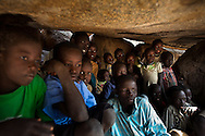 Children take shelter in caves as an Antanov bomber passes overhead in a lethal game they have become used to. Thousands of people have fled to caves to live after repeated bombing attacked by Sudan government forces on civilians areas.