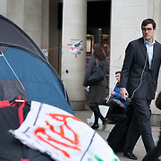 Busy city workers passing the camp site. Day three of the occupation - and the first Monday.  The Occupy London Stock Exchange movement was formed in London in solidarity with the US based Occupy Wall Street. The movements are a respons and in anger to what is seen by many as corporate greed and a failed banking system being bailed out by the public, - which in return are suffering austerity measures to make up for the billions of lost money. The movement occupied the St Paul's Square in the City of London Sat Oct 15 after it failed to secure and occupy Pator Noster Square and the Stock Exchnage itself.