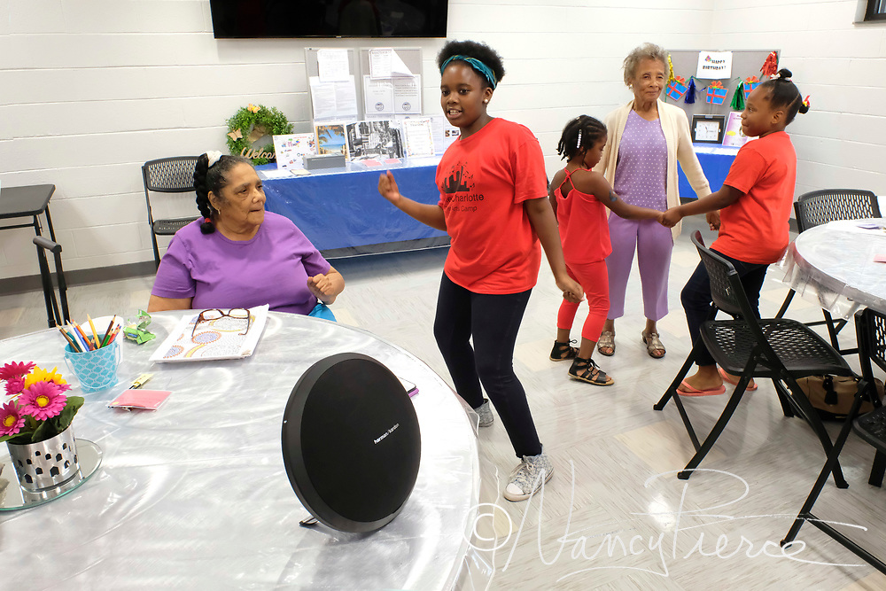 Children from the YMCA Summer Art Camp, which uses the West Charlotte Recreation Center, interact with the seniors who arrive for games, exercise and food, as part of the Camp experience.