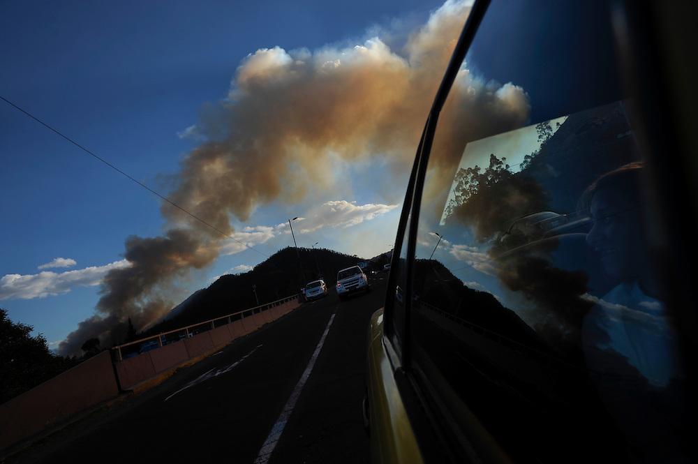 Una periodista mira una columna de humo mientras se dirige a cubrir el incendio de donde proviene. Durante una sequía de dos meses, aproximadamente 2565 incendios forestales, (muchos presuntamente provocados) quemaron 3796 hectareas de bosques, algunas casas y muchos animales silvestres en las laderas boscosas que rodean Quito, la capital del Ecaudor.   Ningún humano murió, pero tomaran décadas antes de que las áreas afectadas se recuperen.