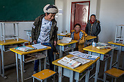 Students search through vacant desks in a classroom of the Ngam-nak school, Tibet (Qinghai, China). Ngam-nak serves as a school for Tibetan nomadic children, who are dropped off by their parents and spend 8 months a year in the remote settlement until they have completed a basic level of education. Staffed by a handful of teachers and cooks, there are no other activities in Ngam-nak apart from the school.