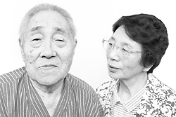 Black and white portrait photograph of uncertain Japanese senior couple