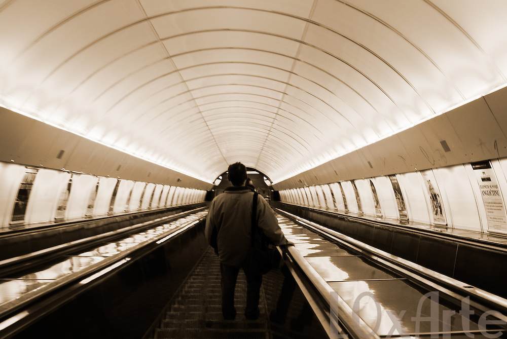 Sepia-toned image of the backs of people travelling down the escalator towards the subway station in the centre of Prague, Czech Republic.