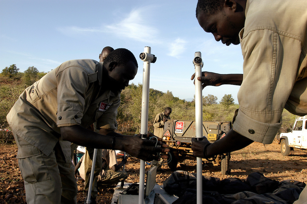 Deminers from Mines Advisory Group (MAG) preparing their equipment to clear anti-personnel landmines at the Kaitap minefield, a former SPLA strong hold and logistics base during the country's long civil war. The site is 800 meters from a small village and widely used for grazing and transit of animals by local residents..Kapoeta, South Sudan. 25/09/2009..Photo © J.B. Russell
