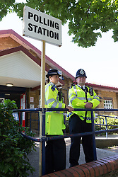 © Licensed to London News Pictures. 11/06/2015. London, UK. Police outside a polling station in Stepney, Tower Hamlets, east London. Tower Hamlets residents go to the polls today to vote for a new Mayor of Tower Hamlets after Lutfur Rahman was removed from office for fraud in corrupt practices by an election court earlier this year. Photo credit : Vickie Flores/LNP